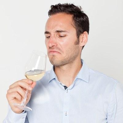 Man drinking bad tasting wine